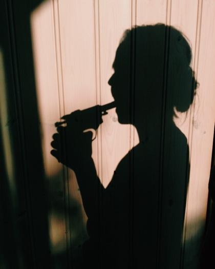 Skuggan av en person som har en pistol i sin mun
